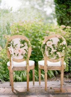 Sillas de una boda decoradas con hiedra en verde y rosas