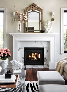 Elegant living room features glass-top coffee table across from light-grey stools atop zebra cowhide rug placed in front of traditional fireplace adorned with white marble surround topped with gilt mirror flanked by polished nickel sconces.