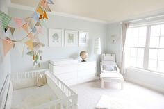White #nursery with colorful pennants.