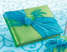 """This colorful 8.5"""" guest book is beautifully crafted with vibrant blues and greens, as well as two color-matched flowers and blue feathers affixed to the front. This guest book has 55 two-sided pages"""