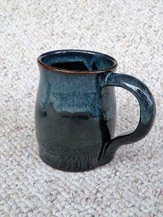 "Stoneware mug by Shelley Duncan, glazed in Cone 6 ""Licorice""with rim dipped in Glossy mottled Dark Green"