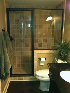 Tiled shower, glass doors with dark frame, half wall