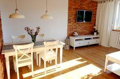 Salon z jadalnią w aranżacji z czerwoną cegłą