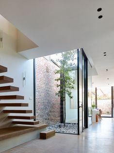 Modern interior with concrete floor, floating stairs, big windows with patio in the middle