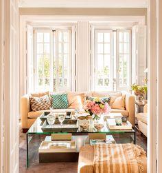 Salón con amplios ventanales, sofá beige y mesa de centro de cristal con flores