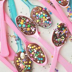 """Zo maak je een kinderfeestjes compleet! Leuk voor bijvoorbeeld een meiden high tea party en zó gemakkelijk te maken. Koop platic lepels in verschillende kleuren, smelt chocolade """"au bain marie"""" of in de magnetron. Schep de gesmolten chocolade in een spuitzak met kleine opening of in een zelfgemaakte spuitzak van bakpapier. Spuit de chocolade op de lepels en strooi er meteen sprinklers naar keuze overheen. Alleen nog laten afkoelen en klaar. Presenteer op een vrolijk gekleurde schaal of op…"""