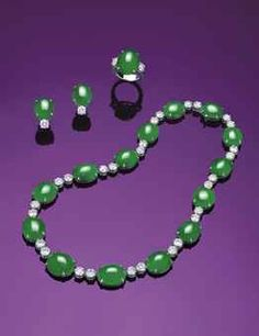A SUITE OF JADEITE AND DIAMOND JEWELLERY  COMPRISING A NECKLACE, SET WITH FOURTEEN OVAL JADEITE CABOCHONS OF EVEN VIVID TO BRILLIANT EMERALD GREEN COLOUR AND HIGH TRANSLUCENCY, ENHANCED BY BRILLIANT-CUT DIAMOND SPACERS; AND A RING AND A PAIR OF EARRINGS EN SUITE, ALL MOUNTED IN 18K WHITE GOLD.