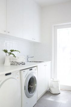 Modern white laundry room features white cabinets paired with white countertops and a white grid tiled backsplash. Modern white laundry room features white cabinets paired with white countertops and a white grid tiled backsplash. Laundry Storage, Grey Flooring, Laundry Mud Room, Stylish Laundry Room, Laundry, White Countertops, Room Layout, Grey Floor Tiles
