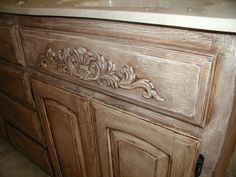 DIY:  Complete instructions on how you can transform a builder grade cabinet into a custom made cabinet with wood appliques and a faux paint finish. wooden applique on master bathroom vanity closeup after