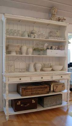 シャビーシックなオープンシェルフに白い食器やグラスを収納。下段には同じテイストの木箱やトランクを置いて、シャビーな雰囲気を壊さずに隠す収納を。