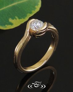 Custom 14kt yellow gold wrap style mounting with .40ct round cut diamond center stone. Carved organic patter on side faces of round shank.