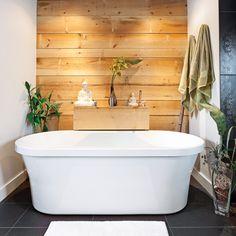 Grand amateur de surf, le propriétaire de cette salle de bain souhaitait créer une ambiance zen et exotique à la façon balinaise. La présence de noir du plancher au plafond et l'intégration de matières naturelles, comme le mur en planches de pin et le dosseret de pierres, évoquent le calme et la spiritualité.