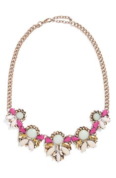 Clusters of faceted crystals sparkle on this colorful statement necklace set on a bright golden chain.