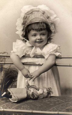 Antique photo of a darling little girl and her doll.