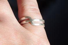 Zilveren ring van vierkant zilverdraad met een speelse bocht. De ring is gematteerd, maar kan natuurlijk ook gepolijst worden. Handgemaakt door Goudsmid, Zilversmid, Edelsmid Marleen van de Kraats, zie 24kraats.nl.