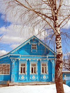 Russian wooden house with carved decorations and a birch tree nearby.