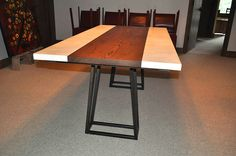 7 foot dining table of white concrete, stained ashe wood slab, and steel base.