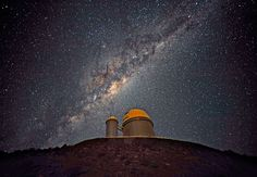 The ESO 3.6-metre telescope at La Silla, during observations, with the telescope's dome lit by the Moon. Across the sky is the plane of the Milky Way, our own galaxy, a disk-shaped structure seen edge-on. Above the telescope dome, and partially hidden behind dark interstellar dust clouds, is the prominent yellowish central bulge of the Milky Way. The plane of the galaxy is populated by hundreds of billions of stars, as well as interstellar gas and dust. The dust absorbs the visible light and…