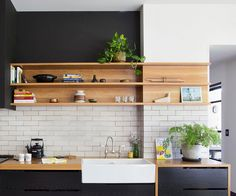Kitchen Modern Black light wood, white range hood, wood cabinets marble island top and