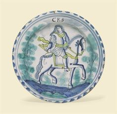 AN ENGLISH DELFT PORTRAIT CHARGER OF CHARLES II  CIRCA 1685  Painted with the Sovereign seated astride a steed and holding a baton, beneath the initials CKS and flanked by sponged trees, within a double blue line and blue-dash rim, on a circular foot  13½ in. (34.2 cm.) diameter