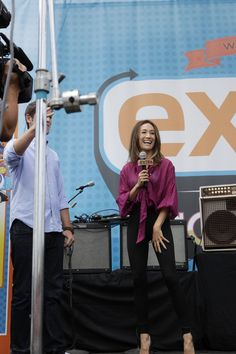 NIKITA's Maggie Q greets fans at the EXTRA Stage at Comic-Con 2012 as a picture of elegance, all smiles and tall high heels (© WBEI. All Rights Reserved.)