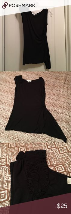 Kenar Black Asymmetrical Top Unique top! Pictures don't do this top justice. It has an adorable rouching design on the left shoulder and also at the right waist (making you look super tiny!). The rouching leads to an asymmetrical cut at the bottom of the shirt. Kenar Tops