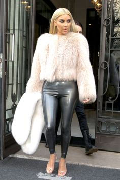Kim K keeps warm in Paris wearing a chic pink fur coat and leather pants.