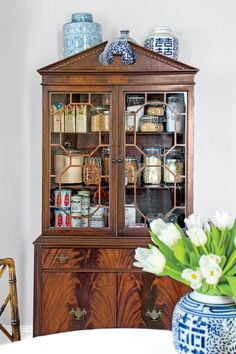 If you're short on square footage, use big family pieces in creative new ways, such as by storing dry goods or miscellaneous supplies in a china cabinet. #homedecor #farmhousestyle #southernliving