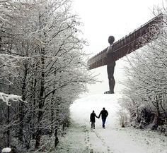 A couple walking in the snow by the Angel of the North