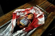 The body of four-year-old Palestinian boy Sahir Abu Namus, who officers said killed in an Israeli air strike, is seen at a hospital morgue