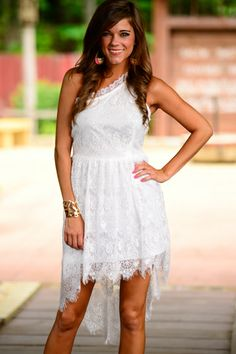 """This dazzling white hi-lo has some gorgeous lace that is just about fit for a bridal veil! The one shoulder style is so chic we can hardly stand it, you will look positively angelic in this beautiful dress! :) Fits true to size. Miranda is wearing the small. Length from shoulder to hem: S- 31"""", M- 31.5"""", L- 32"""""""