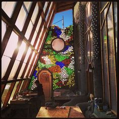 """Bottle ends make for a stunning stained glass statement at the Towers Earthship """"build.""""  This photo is courtesy of the Earthship website http://earthship.com/Designs/earthship-village-ecologies. To learn to do this in a cordwood wall without having to cut the bottles, go to www.cordwoodconstruction.org and click on What's New?"""