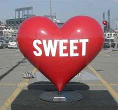 """A BIG RED HEART THAT READS """" SWEET"""" ON IT. THIS ONE OF THOSE ICONIC HEARTS IN SAN FRANCISCO."""