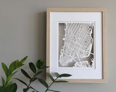 New York City paper cut map framed in shadowbox with mat. Cut on 100lb bristol smooth paper.  11 x 14 shadowbox frame with glass and white beveled edge mat 8 x 10 cut out space  Choose between white, black or blonde frame.