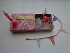 Party in a box.  Bunting, candle, could also add glitter or confetti, and other tiny presents.