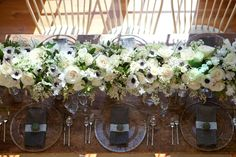 Cream roses, anemones, lily of the valley bush and foliage - a beautiful way to line a bridal table.
