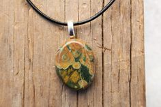 Pretty rainforest rhyolite palm stone necklace. The rainforest rhyolite palm stone is a pendant on a genuine leather cord necklace with a lobster
