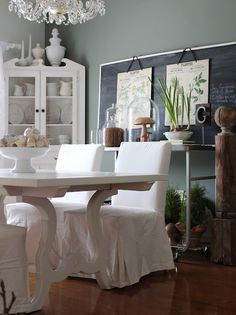 color of the wall contrast with the white table and chairs... chalk board, stainless sideboard, plants and greenery.. love all the organic elements.