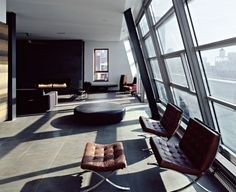 Tan leather barcelona chairs with ottomans... compliments the industrial element of this living room... I like!
