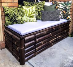 Bamboo garden bench seat with built in storage and tropical foliage print cushions