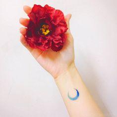 Tiny blue moon spectrum tattoo on the wrist.