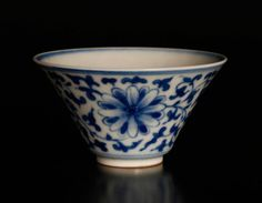 Chinese Blue & White Porcelain Tea Cup The interior with enameled leaf in green, the exterior with floral and scrolling vine designs. Six character mark within two concentric circles in blue on underside.