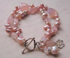 two strands chocked full of this gorgeous pink potpourri bead mix such as faceted rose quartz, chalcedony nuggets, natural pink freshwater pearls, AB/rhinestone rondelles, and oodles of tiny vintage seed beads for flexibility....the ends are finished with sm bali sterling beads and two lovely beaded pearl & blossom charms....thee prettiest pink indeed!    sterling toggle & pearl charm    length ~ 8in