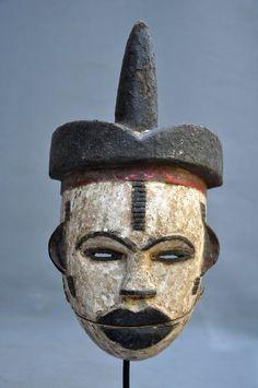 Zogeheten 'talking mask' van de Nigeriaanse Ogoni stam. De onderkaak van het masker is een los deel, vastgemaakt aan de rest en kan bewegen. Vandaar de term 'talking mask'.  Soms is de onderkaak in de vorm van een vogelsnavel. Soms zoals deze. Dit masker verkeert met lichte gebruks- en verouderingssporen in een goede conditie.  Hoogte: 31 cm  Exclusief standaard  Aangetekende verzending
