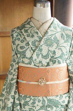 レトロタイルを思わせる澄んだ緑も美しく、繊細な斜め格子と、アラベスクデザインのような優美な唐花模様が一面に染め出された縮緬袷着物です。