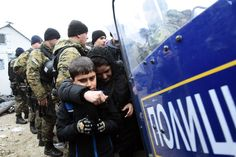 Macedonian policemen stand guard as a woman and a child pass from the northern Greek village of Idomeni to southern Macedonia. Macedonia began allowing only people from Syria, Iraq and Afghanistan to cross its southern border from Greece, while Greek authorities say migrants of other nationalities are gathering on the Greek side of the border and blocking the crossing completely.
