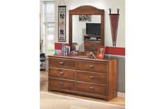 While he might be outgrowing his clothes faster than you like, rest assured the comfortably classic Barchan dresser and mirror set will suit him for years to come. Clean, sophisticated lines blend with a warm and rustic feel, enhanced by a replicated timber cherry grain finish that's got great staying power. Vintage-style copper-color pulls complete the look.
