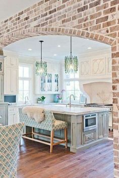 gorgeous kitchen ideas, brick accent wall, custom oven encasement, white and weathered teal, large island, aqua glass pendant lights, orchids, white cabinets, island microwave