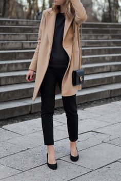 black sweater, pants, and block heels with camel coat More