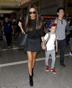 She's still got it: Looking chic in black, Victoria held hands with her little buddy, Cruz...